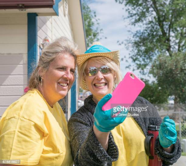 Smiling woman painting house posing for cell phone selfie