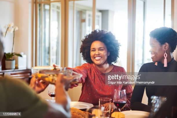 テーブルで友人に食べ物を渡す笑顔の女性 - 公的祝日 ストックフォトと画像