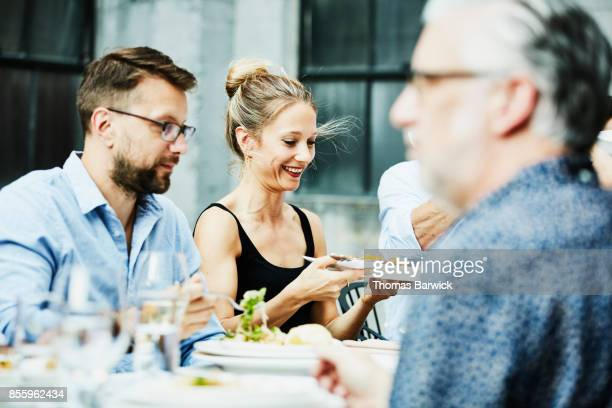 Smiling woman passing platter of food to friend during celebration dinner on outdoor patio