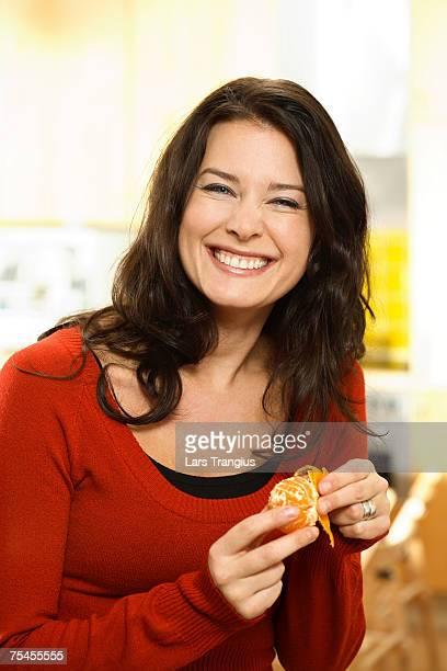 a smiling woman peeling a tangerine. - 皮をむく ストックフォトと画像