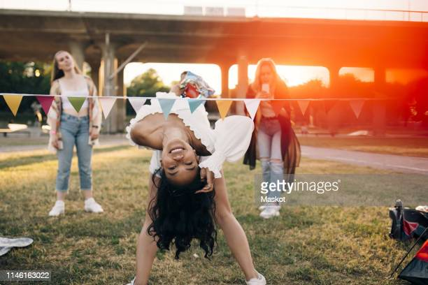 Smiling woman performing limbo dance at lawn in music festival