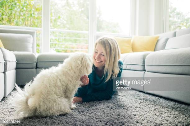 smiling woman petting her dog in living room - respite care stock photos and pictures
