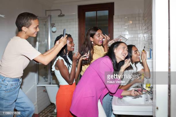 smiling woman photographing friends doing make-up - vijf personen stockfoto's en -beelden
