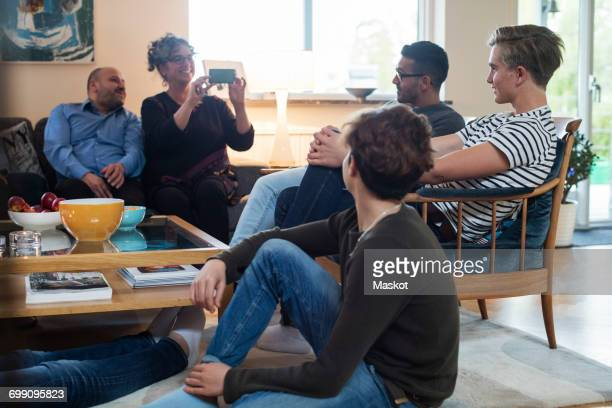 Smiling woman photographing friends while sitting by table in living room