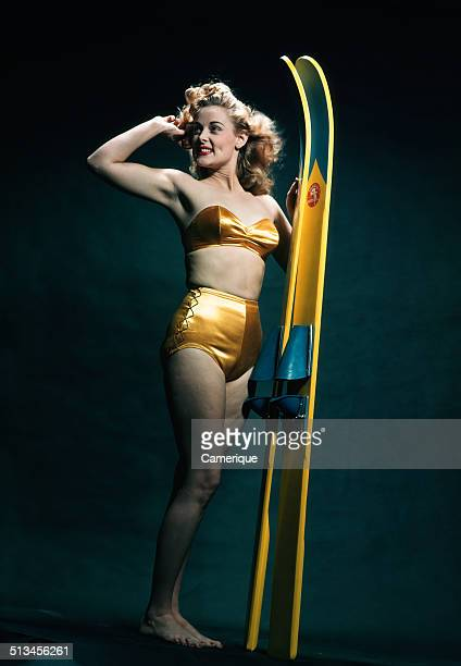 Smiling woman pinup wearing two piece gold bikini bathing suit posing with water skis Los Angeles California 1949