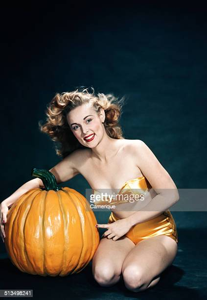 Smiling woman pinup wearing two piece orange bikini posing with pumpkin Los Angeles California 1949