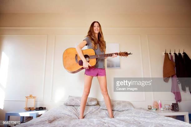 smiling woman playing guitar on bed in bedroom - guitarra imagens e fotografias de stock