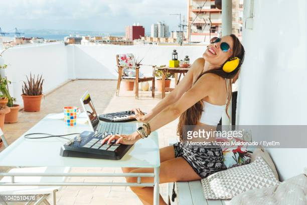 smiling woman playing music in balcony - electronic music stock pictures, royalty-free photos & images