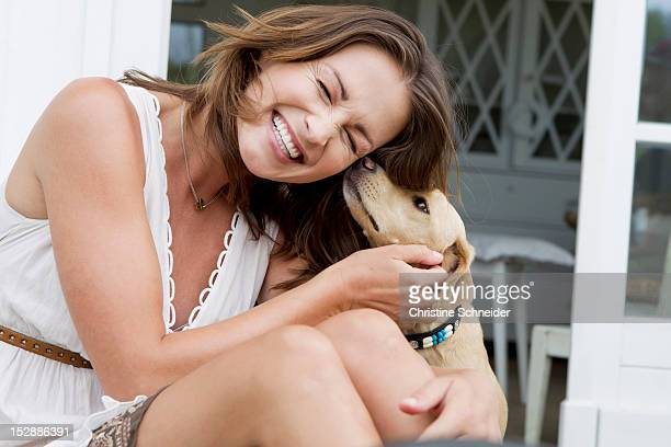 Smiling woman playing with dog