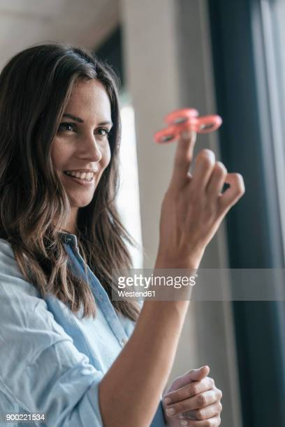 Smiling woman playing with fidget spinner