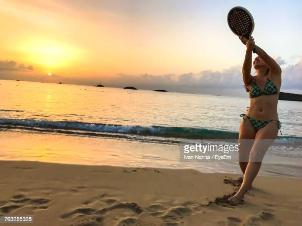 Smiling Woman Playing With Racket On Shore At Beach Against Sky During Sunset