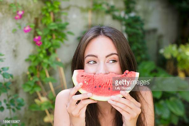 smiling woman playing with watermelon - watermelon stock pictures, royalty-free photos & images