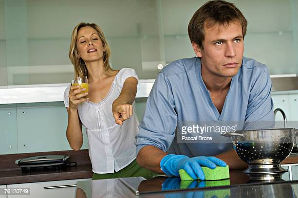 Smiling woman pointing at angry man holding sponge