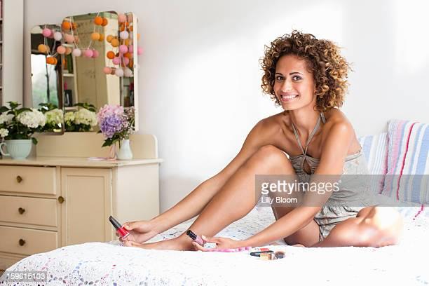 Smiling woman polishing toenails