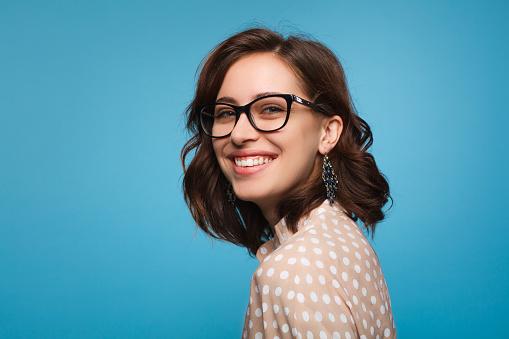 Smiling woman posing in glasses 876629044