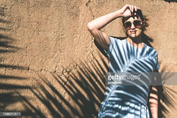 una mujer sonriente posando en una pared de arcilla. sombra de hojas de palma - colección de la moda fotografías e imágenes de stock