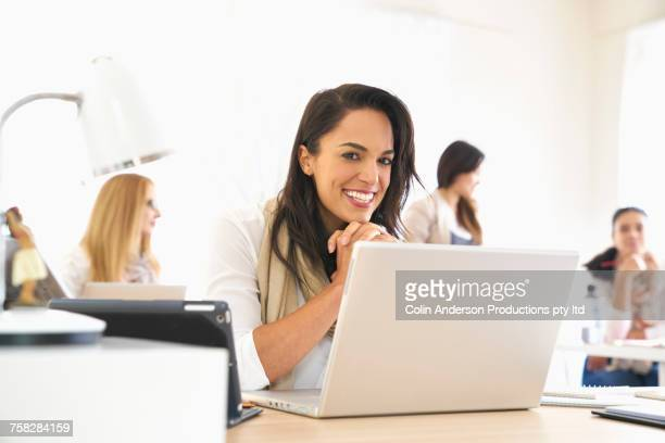 Smiling woman posing with laptop in office