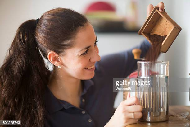 smiling woman pouring coffee powder in glass coffee maker - ground coffee stock photos and pictures