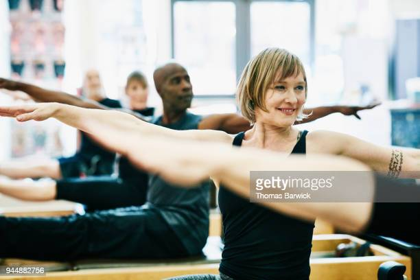 Smiling woman practicing pilates exercises on reformer during class in fitness studio