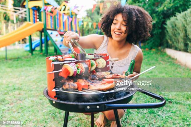 smiling woman preparing barbecue at backyard - grilling stock pictures, royalty-free photos & images