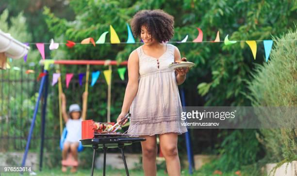 Lachende vrouw voorbereiding barbecue in achtertuin