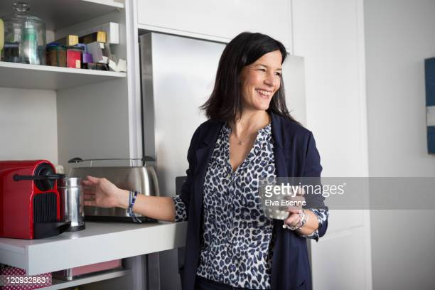 smiling woman preparing coffee in a domestic kitchen - cheveux bruns photos et images de collection