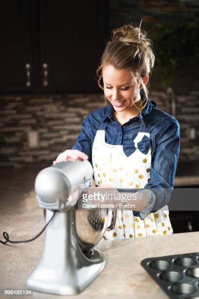 smiling woman preparing food in electric mixer - haushaltsmaschine stock-fotos und bilder