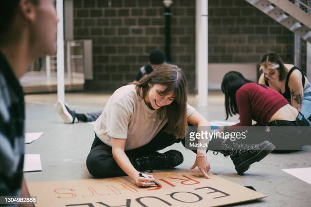 smiling woman preparing signboard while sitting with male and female activists in building - soziale gerechtigkeit stock-fotos und bilder