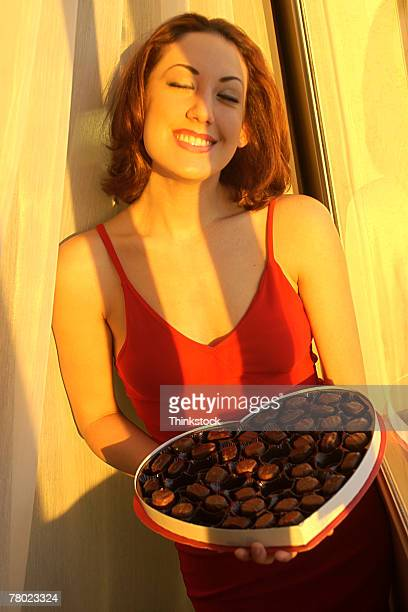 A smiling woman presenting a box of Valentine's Day chocolates to the viewer.
