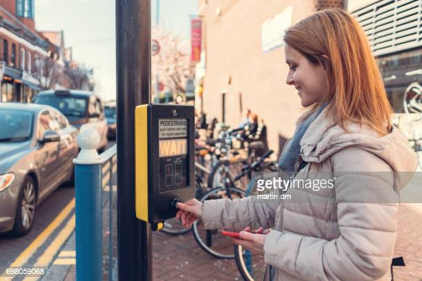 smiling woman pressing the stoplight button at the pedestrian walkway - pedestrian crossing sign stock photos and pictures