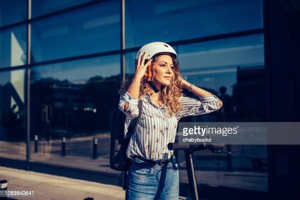 smiling woman puts crash helmet - helmet stock pictures, royalty-free photos & images
