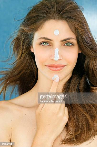 Smiling woman putting cream touches on her face
