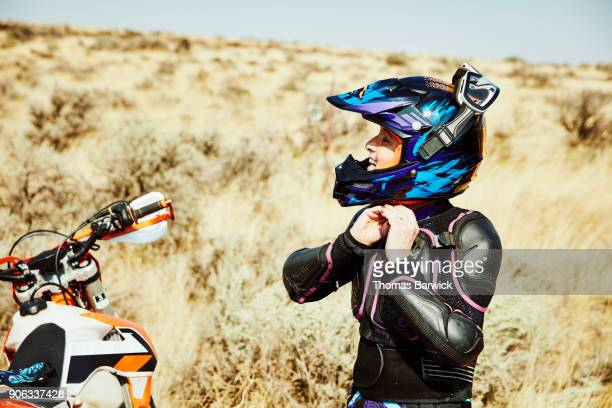 Smiling woman putting on helmet before riding dirt bike in desert