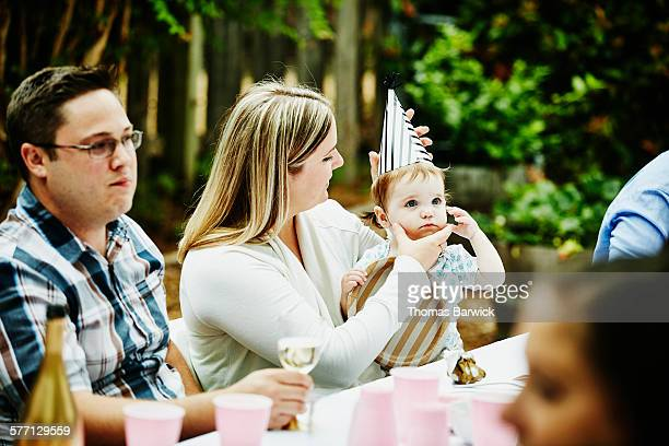 Smiling woman putting party hat on niece