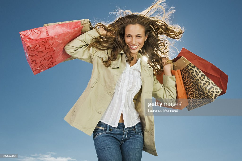 Smiling woman raising up shopping bags in wind : Foto stock