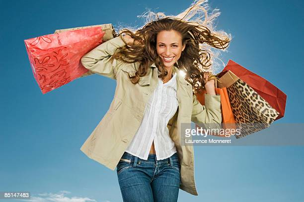 Smiling woman raising up shopping bags in wind