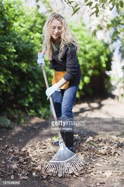 smiling woman raking leaves outdoors - rake stock pictures, royalty-free photos & images