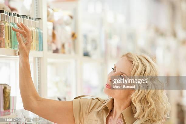 Mujer sonriente alcanzar para perfumes en la tienda de estante