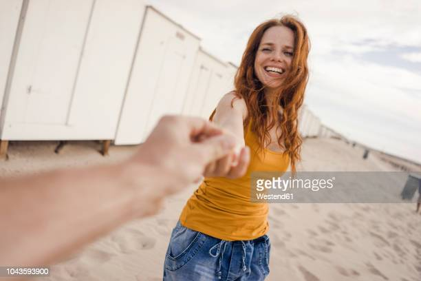 smiling woman reaching out to man's hand - geben stock-fotos und bilder