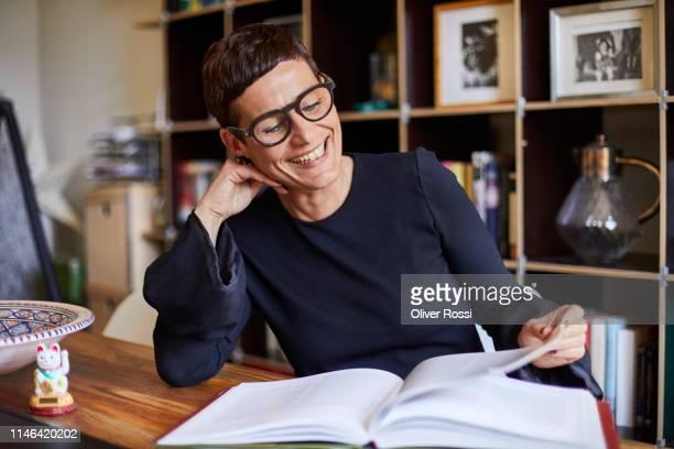 smiling woman reading a book at home - kort haar stockfoto's en -beelden