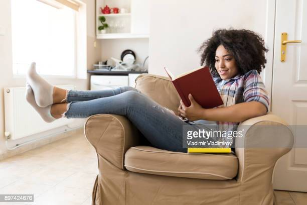 smiling woman reading a book at home - reading stock pictures, royalty-free photos & images