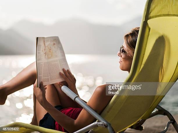 Souriant femme lisant un magazine en chaise longue.