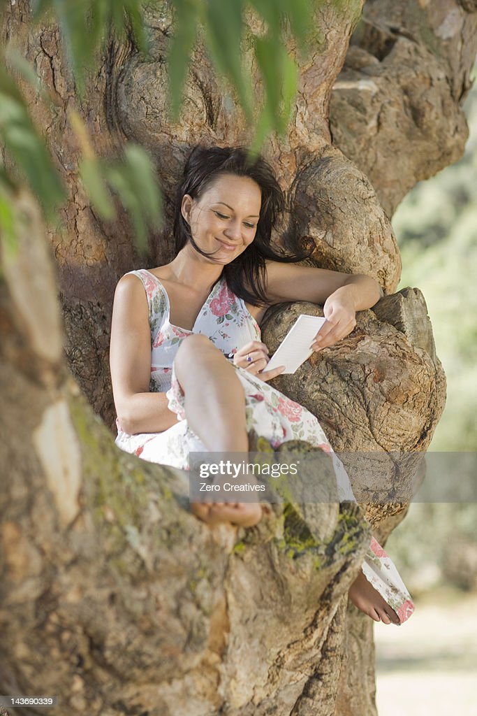 Smiling woman reading in tree : Stock Photo