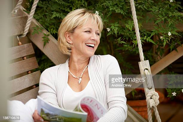 Smiling woman reading magazine