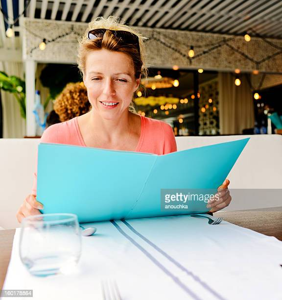Smiling Woman reading menu in a restaurant