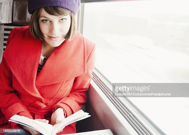 Smiling woman reading on train