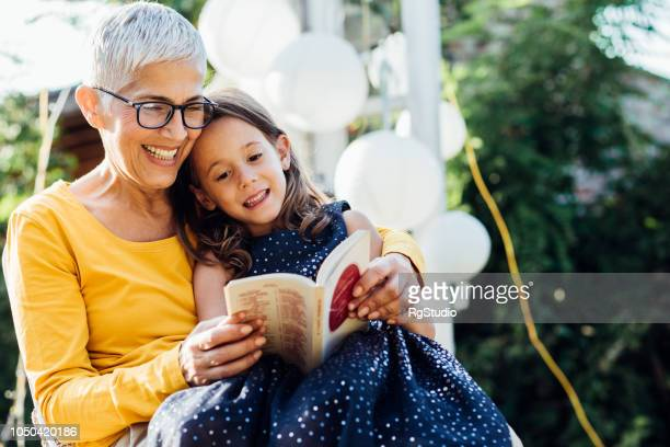smiling woman reading to granddaughter - grandmother stock pictures, royalty-free photos & images