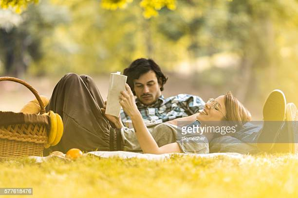 Smiling woman relaxing at picnic with boyfriend and reading book.
