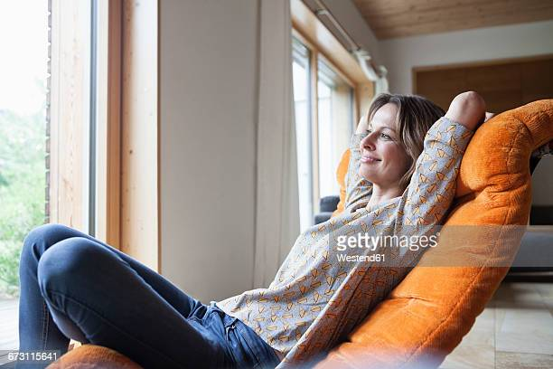 smiling woman relaxing in armchair - hands behind head stock pictures, royalty-free photos & images