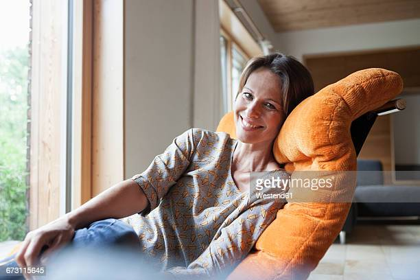 Smiling woman relaxing in armchair